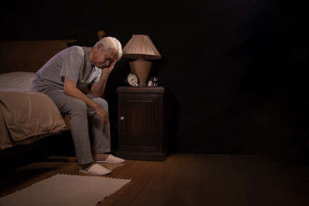 Photo pour Depressed senior person sitting in bed cannot sleep from insomnia - image libre de droit