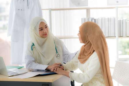 Photo pour Muslim woman patient having consultation with female muslim doctor In clinic - image libre de droit