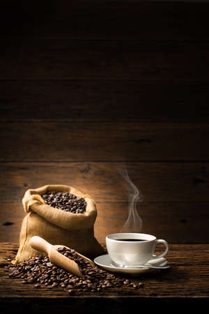 Photo pour Cup of coffee with smoke and coffee beans on old wooden - image libre de droit