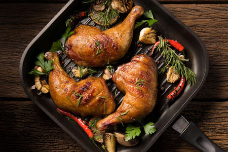 Photo pour Top view of grilled chicken thigh with various vegetables on pan on old wooden - image libre de droit
