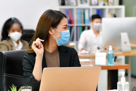 Photo pour Portrait of Asian woman office worker wearing face mask working in new normal office and doing social distancing during corona virus covid-19 pandemic - image libre de droit