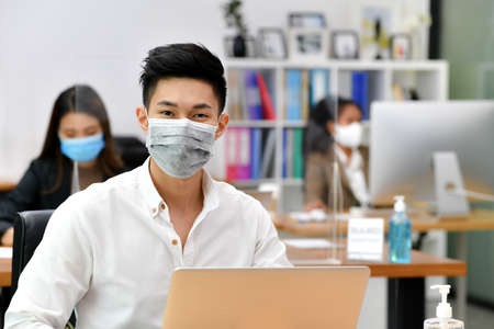 Photo pour Portrait of Asian man office worker wearing face mask working in new normal office and doing social distancing during corona virus covid-19 pandemic - image libre de droit
