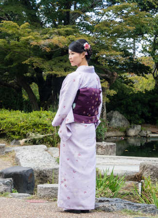 Kyoto, Japan - September 30, 2015: Young girl dressed in colorful kimono in Maruyama park