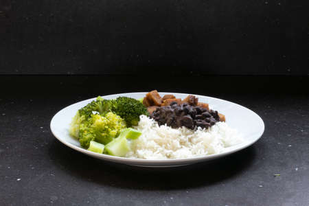 Brazilian food black beans and white rice, broccoli and meat