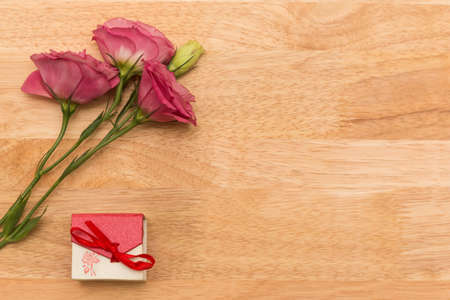 gift with red flower on wooden vintage table with copy space