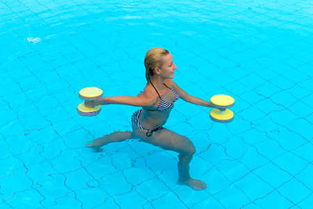 Aqua aerobic. Woman is engaged aqua aerobics in water
