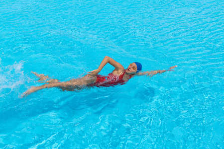 aqua aerobic. Woman swims freestyle in the pool