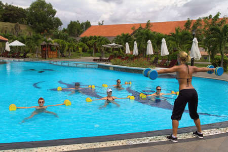 Aqua aerobic. Aqua Gym: aerobics / fitness instructor in front of a group of people in the water performing exercises.