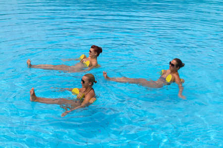 Aqua aerobic. Happy active fitness people doing exercise with aqua dumbbell in a swimming pool