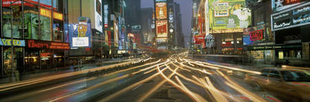 This is Times Square at night. There are streaked lights from the cars traveling through the square. There are neon lights from the billboards as well as signs.
