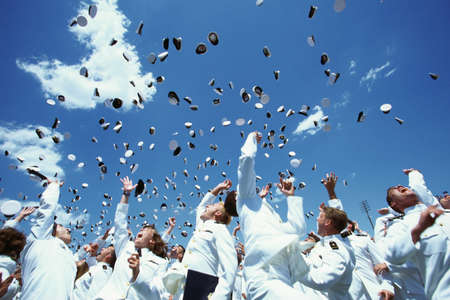 This is the United States Naval Academy Graduation Ceremony. The shows the graduating Naval Cadets during the famous tossing of hats in the air. Their uniforms and hats are all white.
