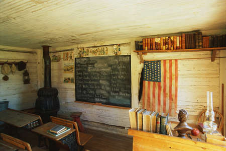 This is the interior of a one room school house. It was the first school in Montana from 1868. There is a black chalkboard and American flag hanging on the wall with a black wood furnace stove in the corner. There are a couple of old fashioned school desk