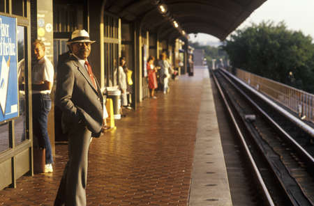 A business man stands waiting for a Metro rail commuter train at sunrise, National Airport, Washington, D.C.