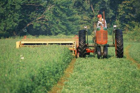 Farmer on a tractor harvesting a field