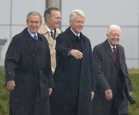 Former U.S. President Bill Clinton waves from the stage accompanied by President George W. Bush, former presidents Jimmy Carter and George H. W. Bush during the official opening ceremony of the Clinton Presidential Library November 18, 2004 in Little Rock