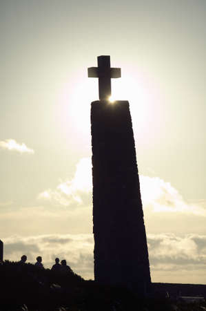 Cross with sun behind it at Cabo da Roca on the Atlantic Ocean in Sintra, Portugal, the westernmost point on the continent of Europe, which the poet Cam›es defined as where the land ends and the sea begins.