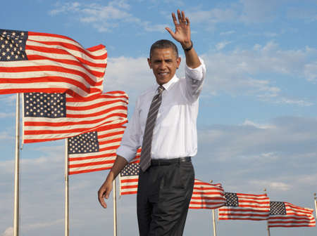 President Barack Obama waving against a backdrop of flags of the United States of America
