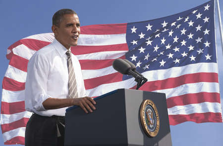 President Barack Obama speaking against a backdrop of the flag of the United States of America