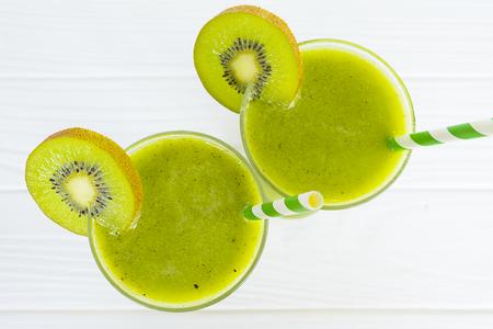 Kiwi smoothies and kiwi fruit on white background from top view