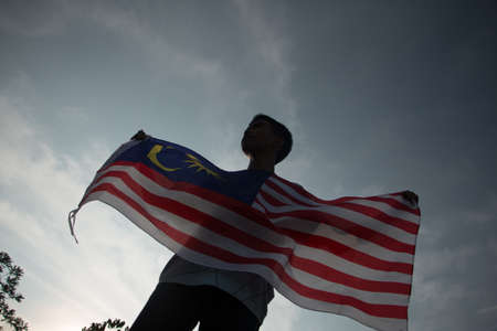 Independence Day concept. A happy and proud citizen holding Malaysian flag. sky background.