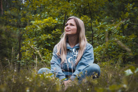 Photo for Woman middle aged meditating in a forest sitting on a grass - Royalty Free Image