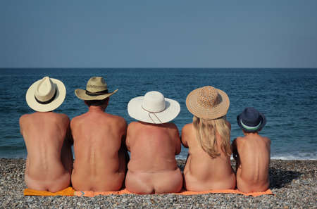 Naked family in hats sitting on the beach