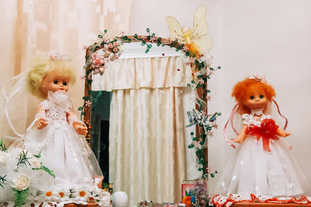 Foto de Two dolls in a dress of the bride on a wall background - Imagen libre de derechos