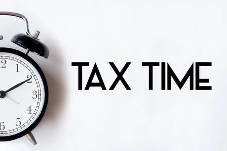 Foto de Tax time word written on white office desk table with alarm clock. - Imagen libre de derechos