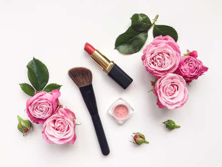 Foto de Decorative flat lay composition with cosmetics and flowers. Flat lay, top view on white background - Imagen libre de derechos