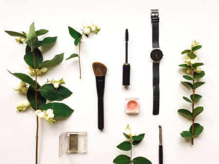 Colorful composition with woman watch, make up tools and accessories, decorated with green snowberry branches and berries. Flat lay on white table, top view, view from above