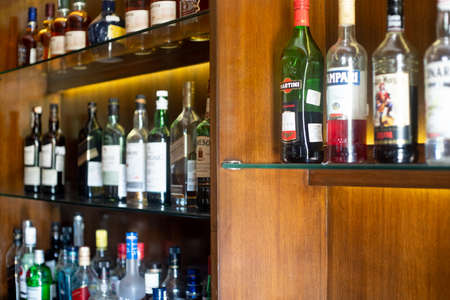 Photo pour Soft focus shot of wooden shelf in a bar pub hotel filled with liqor bottles from top brands of whiskey, gin, rum, vodka and more - image libre de droit