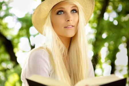 Portrait of a natural and cute woman sitting in on a park bench and reading a book.