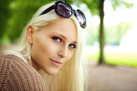 Close up of the face of a sexy blonde lady with sunglasses balanced on top of her forehead in a park.
