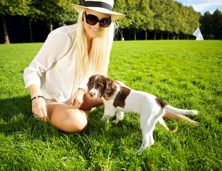 A stylish young blonde woman sits in lush grass playing with her dog in evening sunshine in a park.