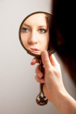 A closeup mirror reflection of a woman's face, selective focus