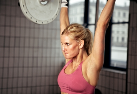 Fitness woman concentrating on lifting heavy weight in gym