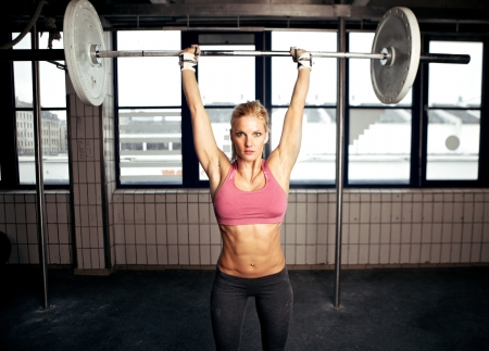 Sexy fit woman performing a shoulder press exercise