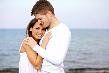 Portrait of a couple cuddling at the beach looking happy