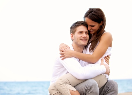 Photo pour Portrait of a handsome guy enjoying the beach together with his girlfriend who is sitting on his lap - image libre de droit