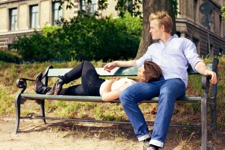 Foto de Romantic young couple resting on the park bench together - Imagen libre de derechos
