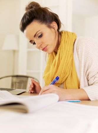 Indoor woman busy writing something and studying all her books