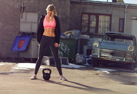 Ghetto girl with kettlebell in a crossfit training outdoor