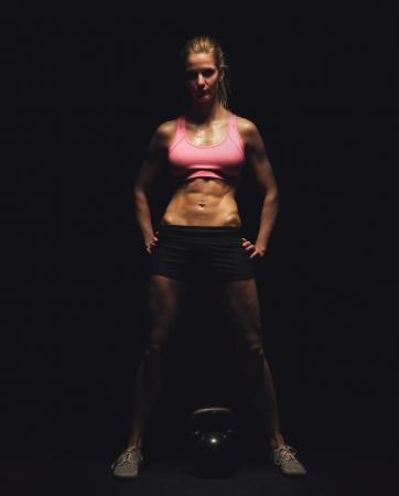 Full length of a female bodybuilder with kettlebell over black background