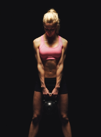 Photo for Fitness woman doing a weight training by lifting a heavy kettlebell - Royalty Free Image