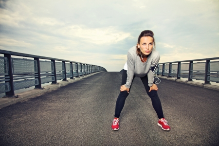 Foto de Focused runner outdoors resting on the bridge - Imagen libre de derechos