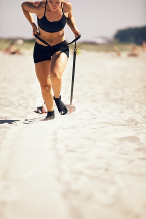 Female crossfitter pulling a sled on sand during crossfit workout
