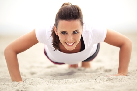 Happy fitness caucasian woman on the beach smiling while doing push up exercise. Active and healthy lifestyle.