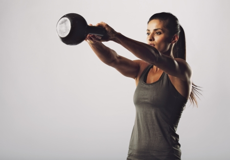 Foto de Image of young attractive female doing kettle bell exercise on grey background. Fitness woman working out. Crossfit exercise. - Imagen libre de derechos