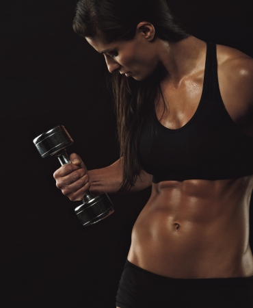 Foto de Female fitness model exercising with dumbbell. Young female bodybuilder working out with hand weights on black background. Woman with muscular body. - Imagen libre de derechos