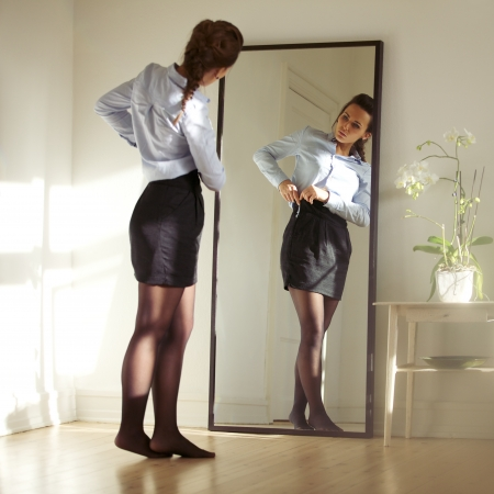 Pretty young businesswoman fixing her skirt in front of mirror. Beautiful caucasian female model getting ready for work.の写真素材
